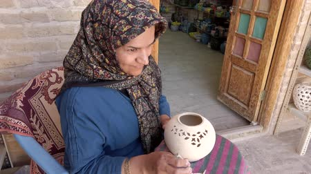 gravure : Isfahan, Iran - 2019-04-12 - Woman Engraves Pottery Prior to Firing.