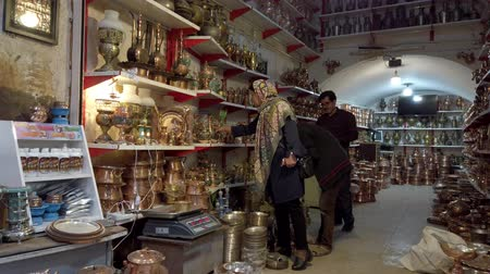 антиквариат : Yazd, Iran - 2019-04-11 -Woman Shops for Copper Items For Home.