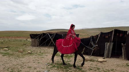 hill tribe : Shiraz, Iran - 2019-04-09 - Qashqai Woman in Red Dress Rides Horse Past Tents.