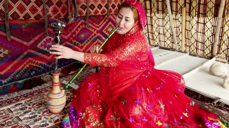 respiração : Shiraz, Iran - 2019-04-09 - Qashqai Woman in Red Dress Inserts Pipe into Water Base And Smokes.