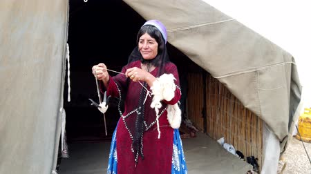 bükülme : Shiraz, Iran - 2019-04-09 - Qashqai Woman Spins Yarn From Goat Wool While Standing.