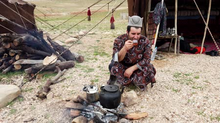 hill tribe : Shiraz, Iran - 2019-04-09 - Qashqai Man Squats and Drinks Tea In Front of Fire.