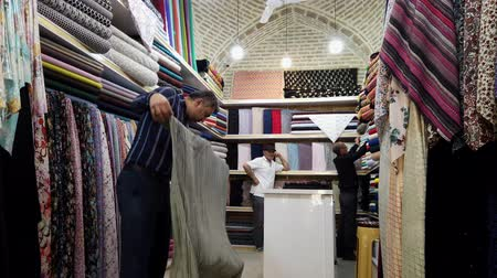 comerciante : Shiraz, Iran - 2019-04-08 - Cloth Merchant Rerolls Product.
