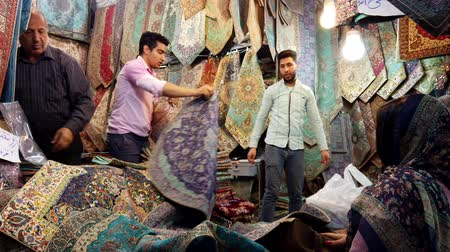 têxteis : Shiraz, Iran - 2019-04-08 - Rug Merchants Show Product to Buyers.