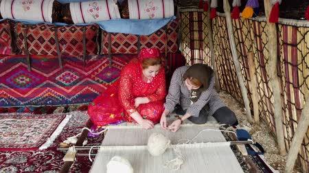 têxteis : Shiraz, Iran - 2019-04-09 - Older Qashqai Woman Teaches Younger Woman How to Weave Carpet.