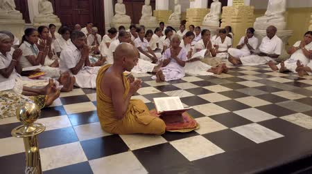 заслуга : Kandy, Sri Lanka - 09-03-24 - Monk Leads Dozens of People Sitting on Floor in Prayer 2 - Side of Monk.