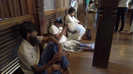 заслуга : Kandy, Sri Lanka - 09-03-24 - People Pray While Sitting in Hall in Tribute to Buddha - Side View.