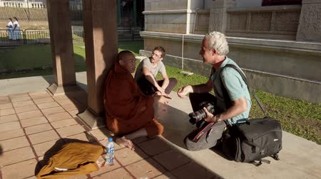 row : Kandy, Sri Lanka - 09-03-24 - Photographer Talking to Monk From Side. Stock Footage