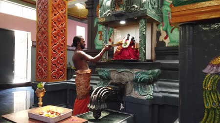 шри : Nuware, Sri Lanka - 2019-03-26 - Hindu Priest Gives Offering to God Statue.