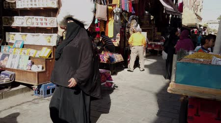 kahire : Cairo, Egypt - 2019-05-03 - Busy Bizaare Street With Woman in Hijab Carrying Package on Head.