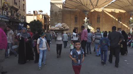 market vendor : Cairo, Egypt - 2019-05-03 - Busy Bizaare Street With Boy Carrying Huge Load of Bread on Head. Stock Footage