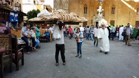 market vendor : Cairo, Egypt - 2019-05-03 - Bizaare Street With Boy Carrying Huge Load of Bread on Head.