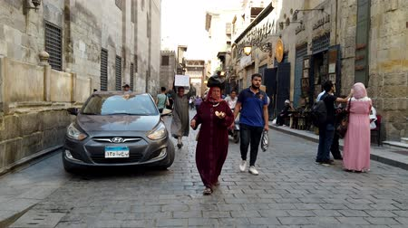 carrello spesa : Cairo, Egypt - 2019-05-03 - Busy Bizaare Street With Woman Eating While Carrying Goods on Her Head. Filmati Stock
