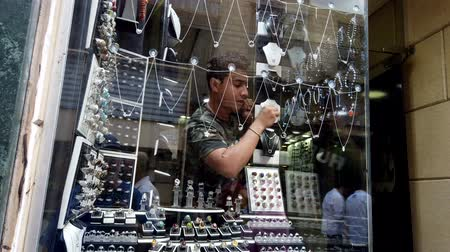 バルカン半島 : Cairo, Egypt - 2019-05-03 - Busy Bizaare Street Reflected in Window as Man Arranges Jewelry Display. 動画素材