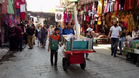 kolejka : Cairo, Egypt - 2019-05-03 - Busy Bizaare Street With Food Cart Rolling Past.