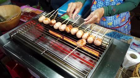 укроп : Phayao, Thailand - 2019-03-08 - Food Vendor Rotates Chicken Sausage on Stove.