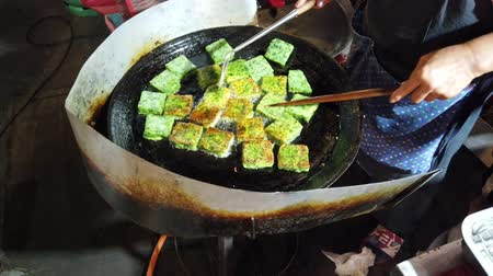 kiełbasa : Phayao, Thailand - 2019-03-08 - Food Vendor Rotates Vegetarian Snack in Oil on Stove.