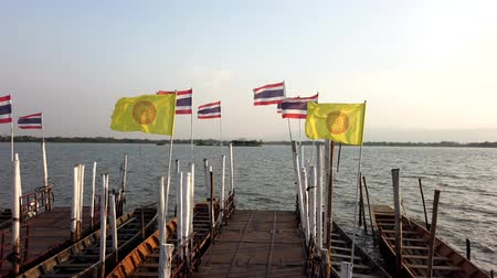 эмблема : Phayao, Thailand - 2019-03-08 - Many Thailand and Buddhist Flags Flying on Pier.