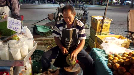 malásia : Phayao, Thailand - 2019-03-08 - Food Vendor Cuts Coconut Open.