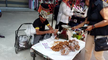 saŁata : Chiang Saen, Thailand - 2019-03-10 - Man Sits at Table and Sells Sugar.