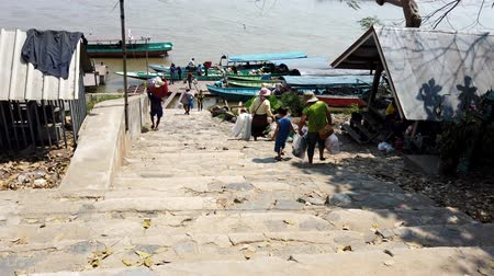 saŁata : Chiang Saen, Thailand - 2019-03-10 - People Load Baskets of Vegetables Down Steps and Onto Long Boat.