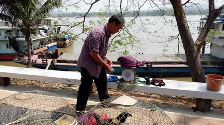 comerciante : Chiang Saen, Thailand - 2019-03-10 - Man Hands Over Live Ducks to a Customer at a Market.