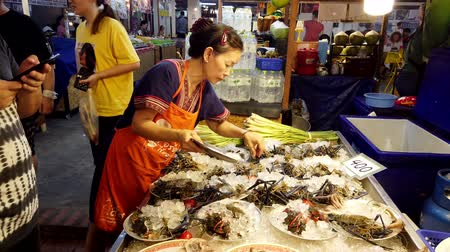 to take : Chiang Mai, Thailand - 2019-03-15 - Woman Ices Seafood Plates at Market.