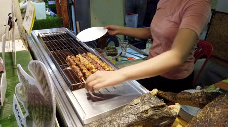tomar : Chiang Mai, Thailand - 2019-03-15 - Aligator Meat is Cooked at Market - Rotated Side View.