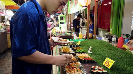 comerciante : Chiang Mai, Thailand - 2019-03-15 - Man Chooses Pieces of Sushi at Market Stall.