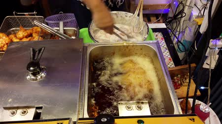 prodejce : Chiang Mai, Thailand - 2019-03-15 - Chicken is Added to Deep Fryer at Market.