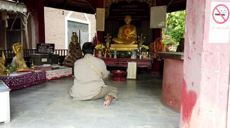 cassock : Chiang Mai, Thailand - 2019-03-15 - Woman Sits On Floor And Prays to Buddha.