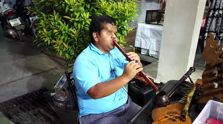 mikrofon : Chiang Rae, Thailand - 2019-03-13 - One Eyed Blind Man Plays Flute in Market For Spare Change.