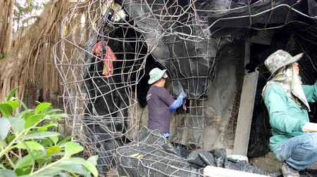 ladrillo : Chiang Rae, Thailand - 2019-03-13 - White Temple Construction - Man Prepares Wire Frame For New Shrine. Archivo de Video