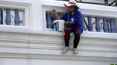 naprawa : Bangkok, Thailand - 2019-03-02 - Woman Touches up Paint on Balcony of Grand Palace.