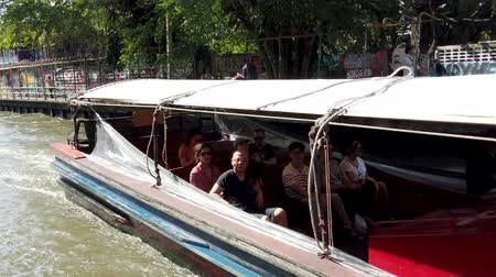 busy line : Bangkok, Thailand - 2019-03-03 - Long Canal Boat Ferry Passes and Then Docks.