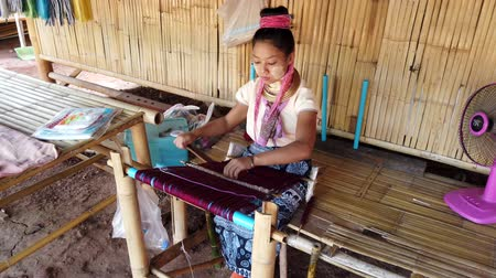 племенной : Bangkok, Thailand - 2019-03-03 - Long Neck Karen Tribe Woman 4 - Woman Weaves Tapestry on Her Loom Close View. Стоковые видеозаписи
