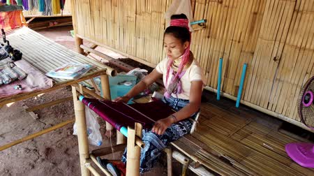minoria : Bangkok, Thailand - 2019-03-03 - Long Neck Karen Tribe Woman 1 - Woman Weaves Tapestry on Her Loom. Stock Footage
