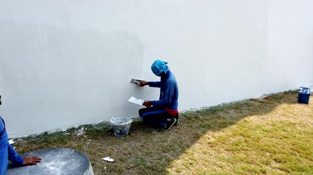 naprawa : Bangkok, Thailand - 2019-03-02 - Man Applies Stucco To Grand Palace Outer Wall For Maintenance.