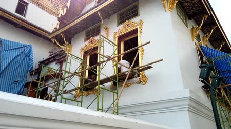 reparatie : Bangkok, Thailand - 2019-03-02 - Two Men Apply Gold Trim Paint to Grand Palace For Maintenance.