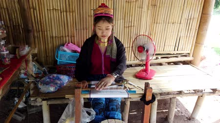 szövetek : Bangkok, Thailand - 2019-03-03 - Long Neck Karen Tribe Woman 2 - Woman Weaves Tapestry on Her Loom Front View.