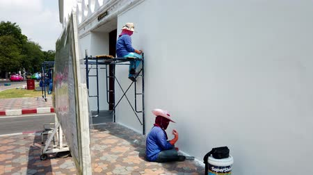 kielnia : Bangkok, Thailand - 2019-03-02 - Woman Applies Stucco To Grand Palace Outer Wall For Maintenance.