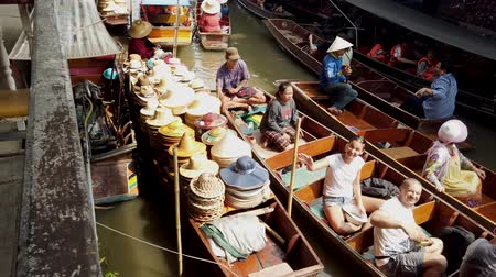 megtöltött : Bangkok, Thailand - 2019-03-03 - Tourist Canal Boats Pass Vendor Boat Filled With Hats. Stock mozgókép