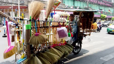 sprzątanie : Bangkok, Thailand - 2019-03-17 - Market Vendor of Brushes and Brooms Rides by on Motorcycle Cart.