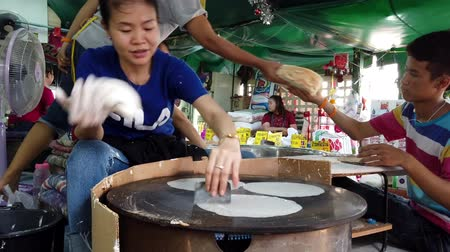 piekarz : Bangkok, Thailand - 2019-03-17 - Woman Rapidly Spreads and Cooks Flour Based Sweets on Grill at Market.