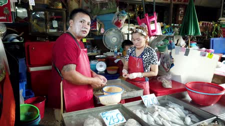 lokaal : Bangkok, Thailand - 2019-03-17 - Man and Woman Peel Shrimp at Market.