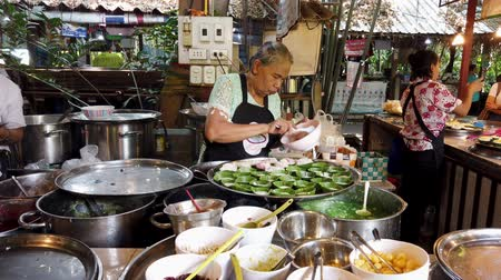 ısıtma : Bangkok, Thailand - 2019-03-17 - Woman Scoops Pudding Into Leaf Bowls at Market. Stok Video