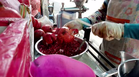 frutoso : Bangkok, Thailand - 2019-03-17 - Market Vendor Extracts Pomegranate Seeds For Juice.