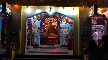 vallási : Kataragama, Sri Lanka - 2019-03-29 - Buddha Statue is Backed by Gaudy Light Display.