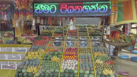 banan : Kataragama, Sri Lanka - 2019-03-29 - Fruit and Vegetable Stand With Asian Advertising Text Scrolling Above.