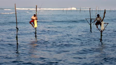 yerler : Galle, Sri Lanka - 2019-04-01 - Stilt Fishermen - Two Men Flipping Poles.